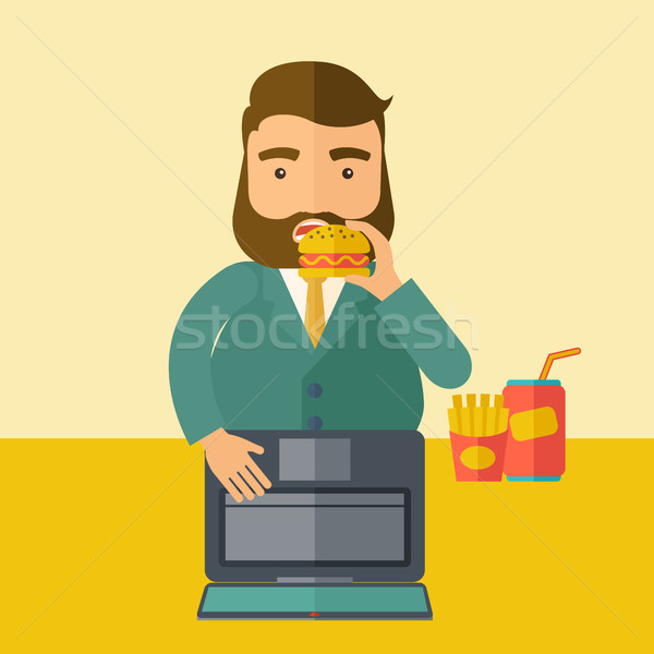 Young fat guy eating while at work. Stock photo © RAStudio