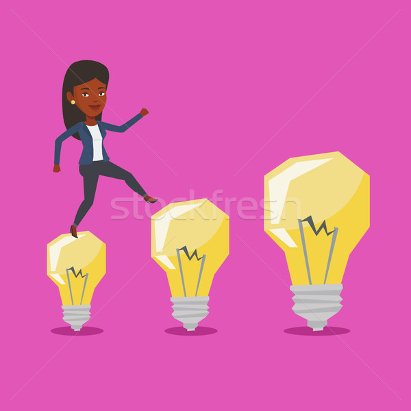 Business woman jumping on idea light bulbs. Stock photo © RAStudio