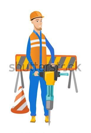 Young builder using pneumatic hammer. Stock photo © RAStudio