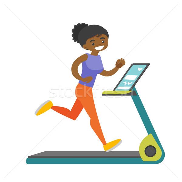 Young african-american woman running on treadmill. Stock photo © RAStudio