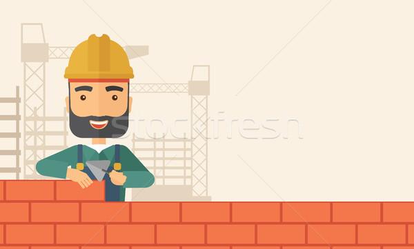 Builder man is building a brick wall. Stock photo © RAStudio