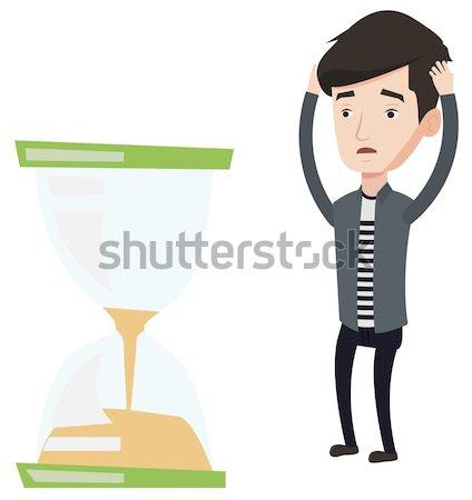 Desperate businesswoman looking at hourglass. Stock photo © RAStudio