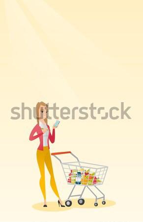 African woman walking with shopping trolley. Stock photo © RAStudio