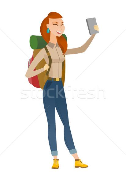Traveler woman with backpack making selfie. Stock photo © RAStudio