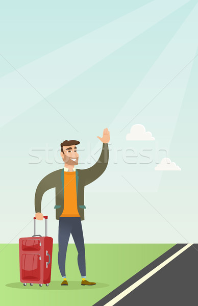 Young caucasian man with suitcase hitchhiking. Stock photo © RAStudio