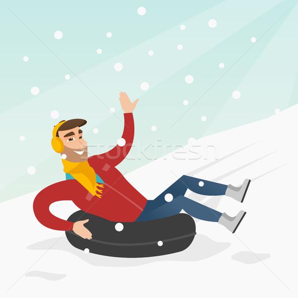 Man sledding on snow rubber tube in the mountains Stock photo © RAStudio