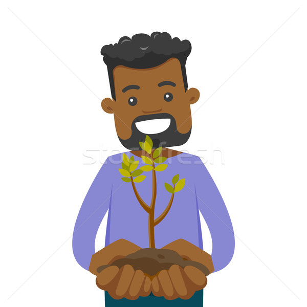 African-american man holding green plant in soil. Stock photo © RAStudio
