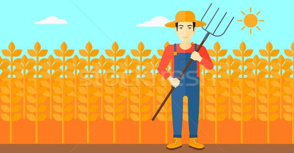Farmer with pitchfork. Stock photo © RAStudio