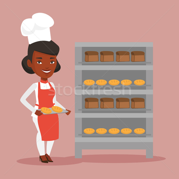 Happy young female baker holding tray of bread. Stock photo © RAStudio