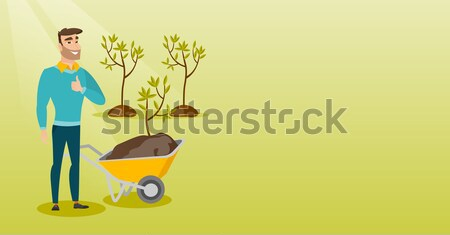 Man pushing wheelbarrow with plant. Stock photo © RAStudio