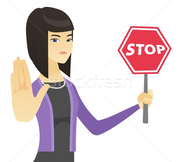 Asian business woman holding stop road sign. Stock photo © RAStudio