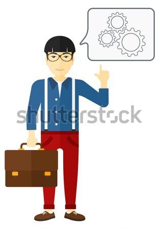 Businessman pointing at cogwheels. Stock photo © RAStudio