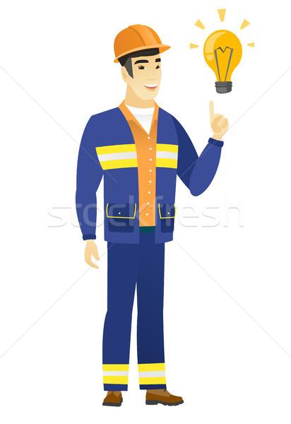 Builder pointing at bright idea light bulb. Stock photo © RAStudio