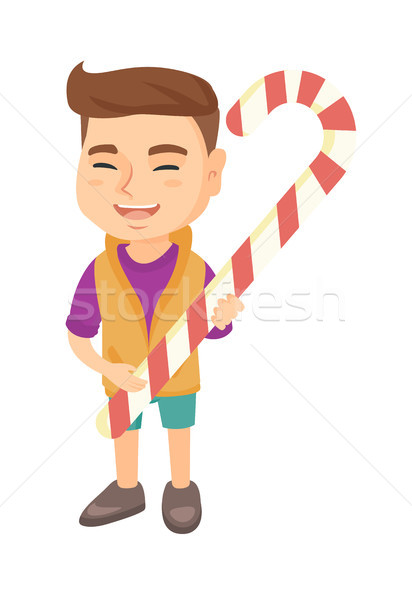 Caucasian little boy holding christmas candy cane. Stock photo © RAStudio