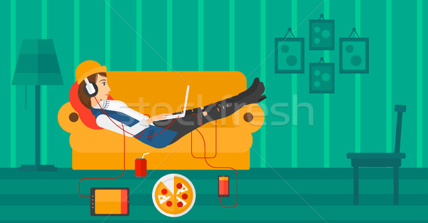 Woman lying on sofa with many gadgets. Stock photo © RAStudio