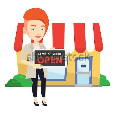 Female shop owner holding open signboard. Stock photo © RAStudio