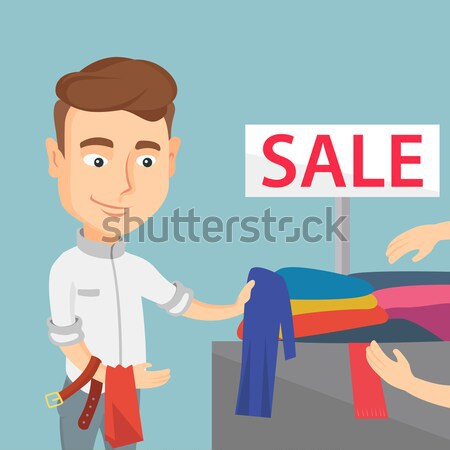 Young man choosing clothes in shop on sale. Stock photo © RAStudio