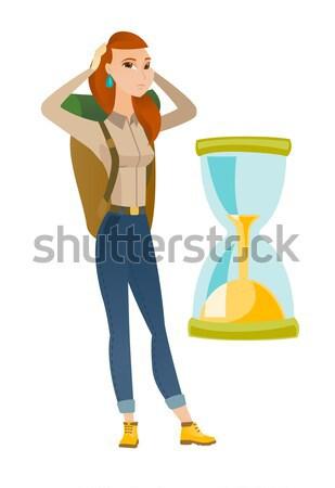 Worried asian traveler woman looking at hourglass. Stock photo © RAStudio