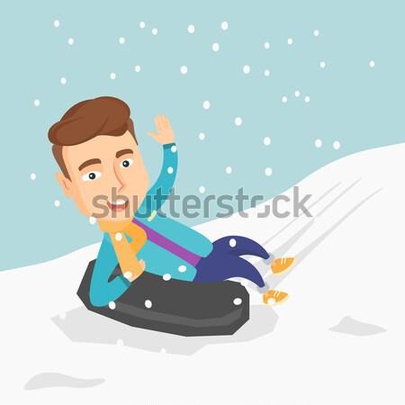 Man sledding on snow rubber tube in the mountains. Stock photo © RAStudio