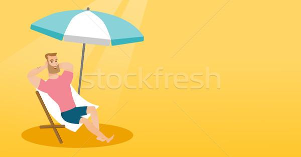 Young caucasian man relaxing on the beach chair. Stock photo © RAStudio