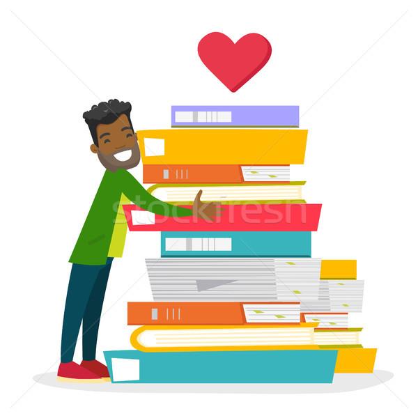 Young african-american man hugging books. Stock photo © RAStudio