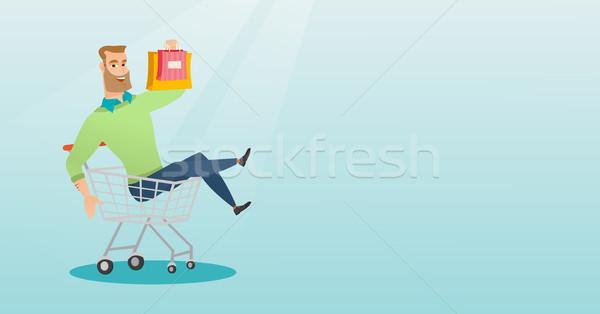 Young caucasian man riding in shopping trolley. Stock photo © RAStudio