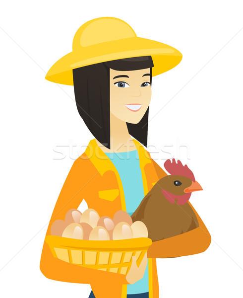 Asian farmer holding chicken and basket of eggs. Stock photo © RAStudio