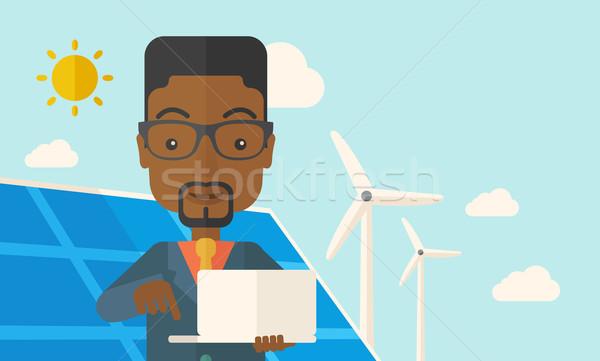 African man with laptop in solar panel. Stock photo © RAStudio