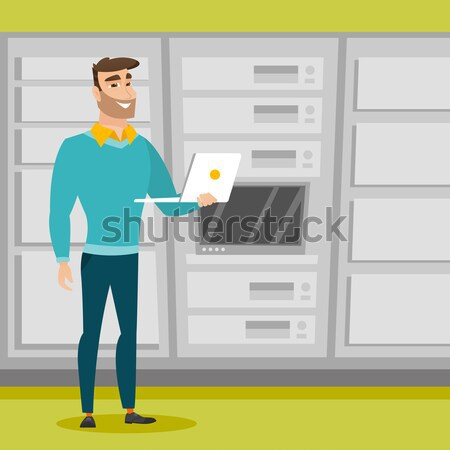 Engineer working on laptop in network server room. Stock photo © RAStudio
