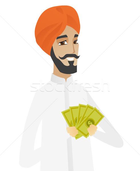 Happy hindu businessman holding money. Stock photo © RAStudio