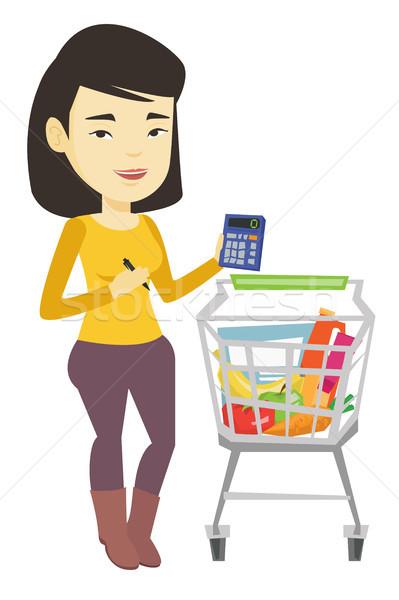 Female customer counting on calculator. Stock photo © RAStudio