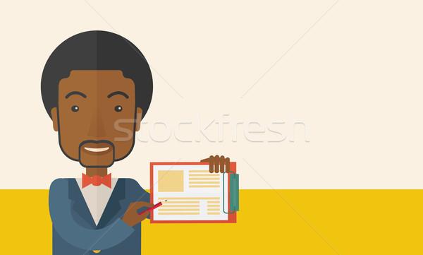 Handsome black guy holding clipboard. Stock photo © RAStudio