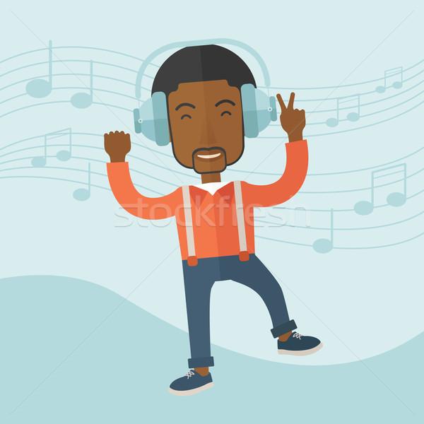 Happy young man dancing while listening to music. Stock photo © RAStudio