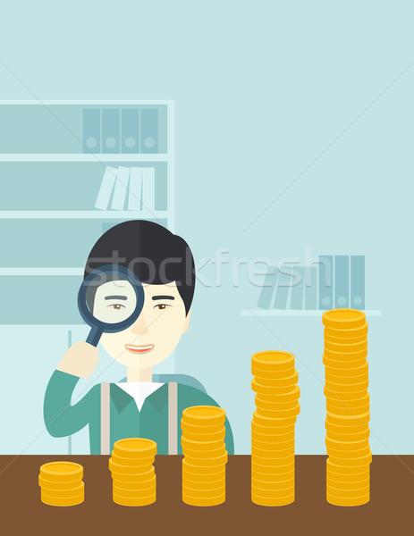 Japanese man looking at his growing business using magnifying glass. Stock photo © RAStudio