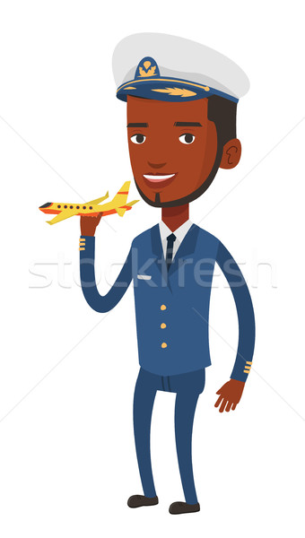Cheerful airline pilot with model of airplane. Stock photo © RAStudio
