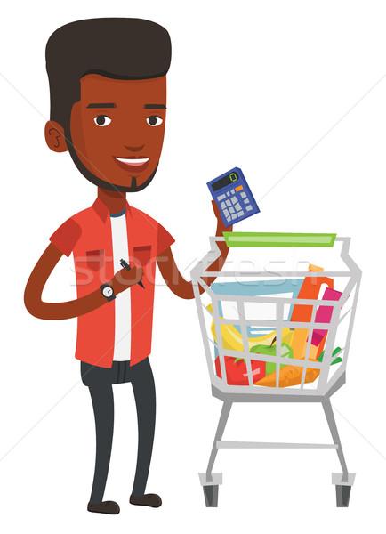 African man counting prices on calculator. Stock photo © RAStudio