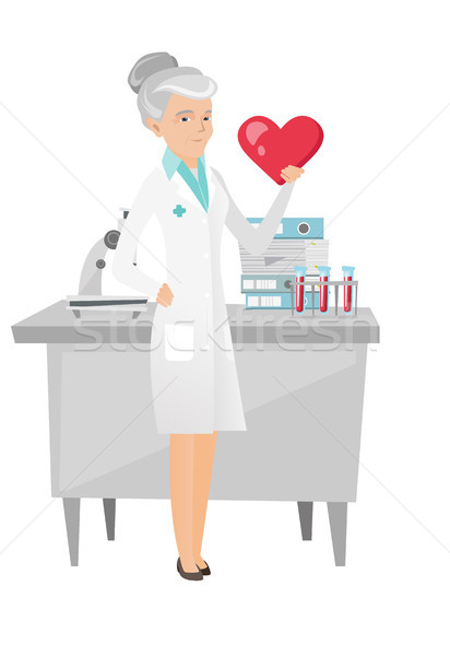 Caucasian cardiologist holding a big red heart. Stock photo © RAStudio