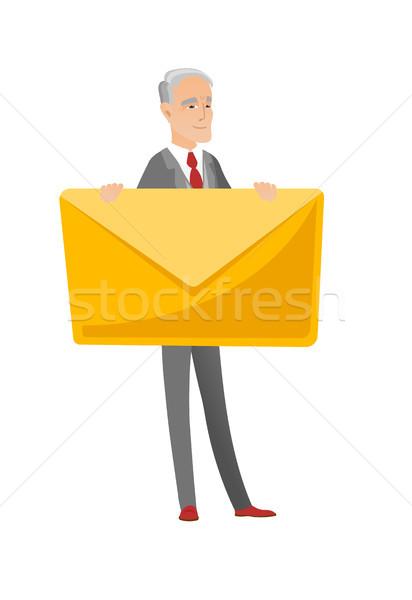 Senior caucasian businessman holding big envelope. Stock photo © RAStudio