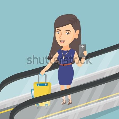 Vrouw smartphone roltrap luchthaven permanente koffer Stockfoto © RAStudio