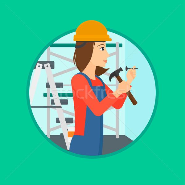 Worker hammering nail. Stock photo © RAStudio