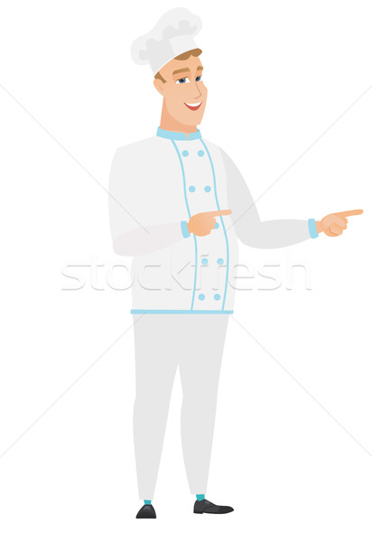 Young caucasian chef cook pointing to the side. Stock photo © RAStudio