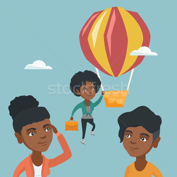 Hardworking employee flying away on a balloon. Stock photo © RAStudio