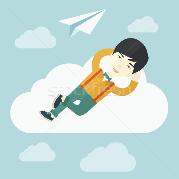 Asian man lying on a cloud with paper plane. Stock photo © RAStudio