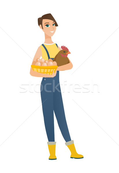 Farmer holding chicken and basket of eggs. Stock photo © RAStudio