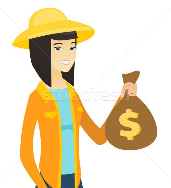 Fiatal ázsiai gazda tart pénz táska Stock fotó © RAStudio