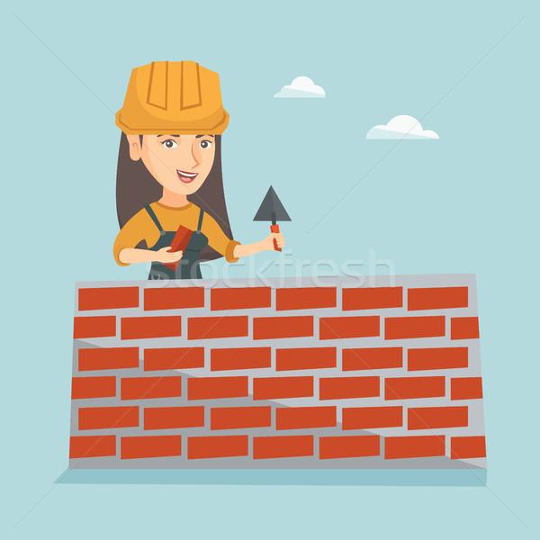 Young caucasian bricklayer building a brick wall. Stock photo © RAStudio