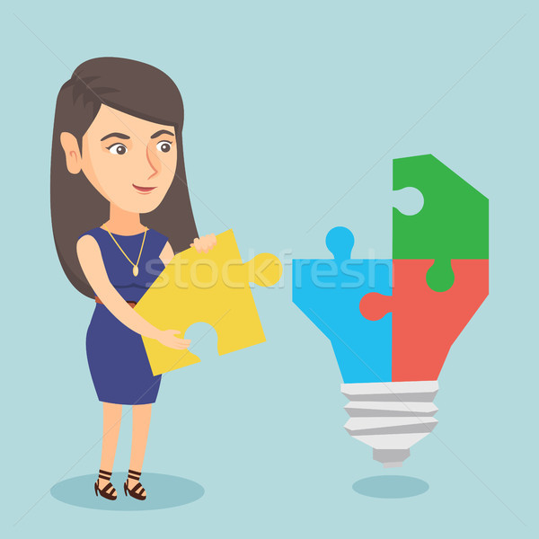 Businesswoman completing lightbulb made of puzzle. Stock photo © RAStudio