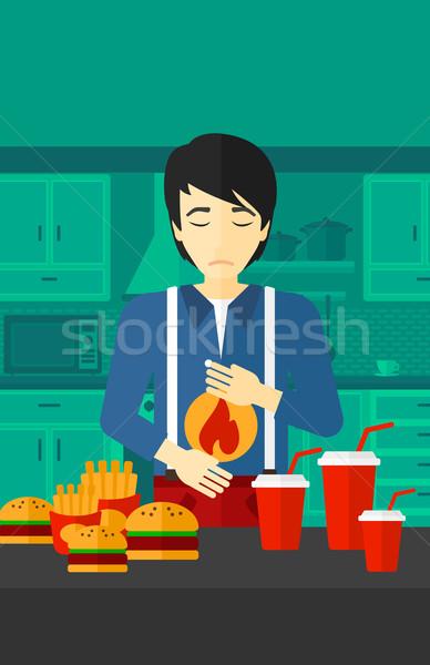 Uomo sofferenza bruciore di stomaco asian piedi tavolo da cucina Foto d'archivio © RAStudio