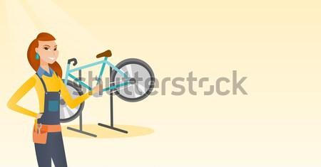 Caucasian bicycle mechanic working in repair shop. Stock photo © RAStudio