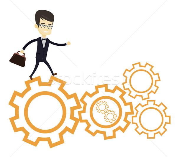 Business man running on cogwheels. Stock photo © RAStudio